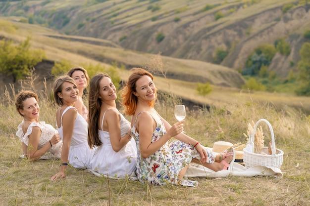 Het gezelschap van vrolijke vriendinnen in witte jurken kijkt uit op de groene heuvels