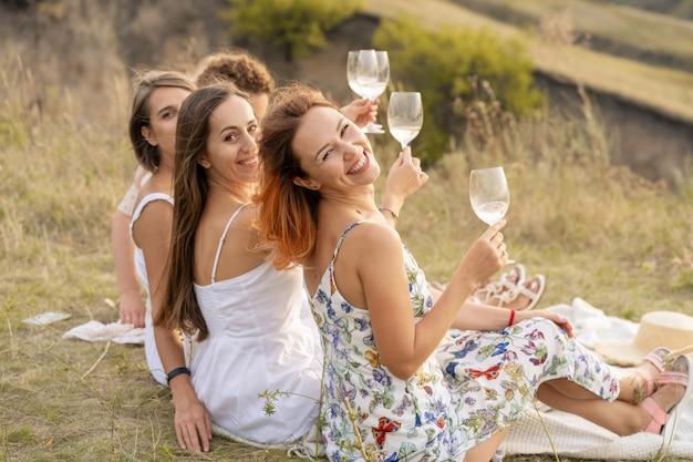 Het gezelschap van vrouwelijke vrienden die plezier hebben en genieten van een zomerse groene picknick en glazen heffen met wijn. mensen concept.