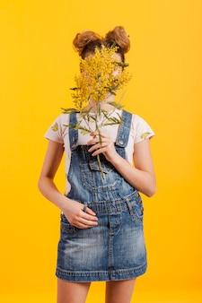 Het gezicht van de het meisjesdekking van het portret met bloementakken