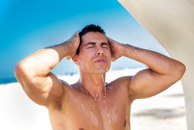 Het gezicht van de mensenwas met koud water na het zonnebaden bij strand