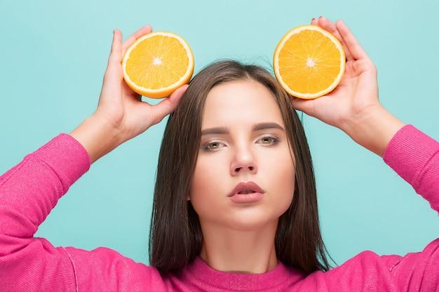 Het gezicht van de mooie vrouw met sappige sinaasappel
