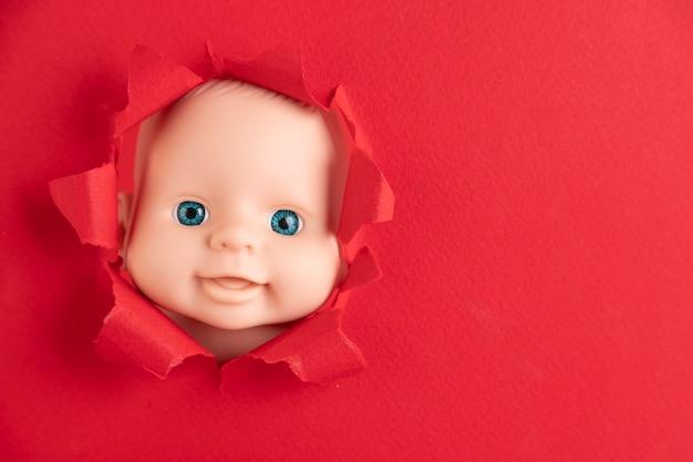 Het gezicht van de pop gluurt uit achter stukjes rood papier, close-up. ruimte kopiëren.