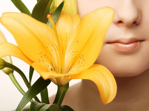 Het gezicht van de schoonheidsvrouw met gele leliebloem