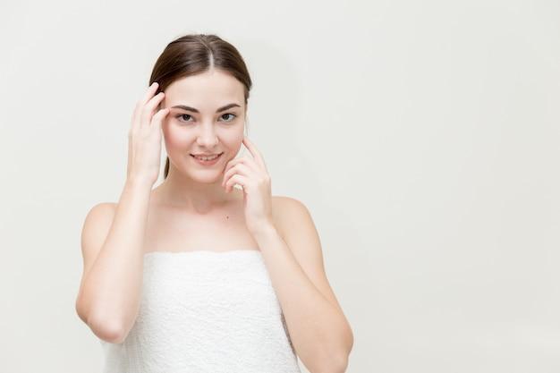 Het gezicht van de schoonheidsvrouw met hand stelt haar die gezichtsvorm voor op witte studio wordt geïsoleerd