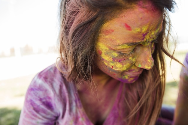 Het gezicht van de vrouw bedekt met holi-kleur