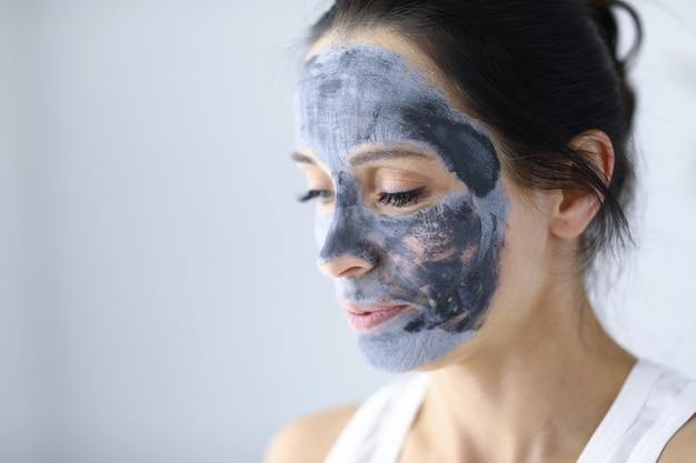 Het gezicht van de vrouw is bedekt met een cosmetisch masker van klei voor huidverjonging