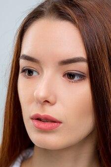 Het gezicht van de vrouw op een grijze achtergrond