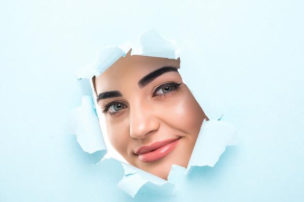 Het gezicht van een jonge mooie vrouw met een lichte make-up en gezwollen blauwe lippen tuurt in een gat in blauw papier.