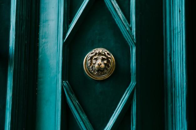 Het gezicht van een leeuw in vergulding op een groene deur in een ruit