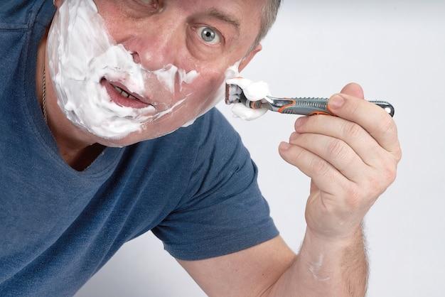 Het gezicht van een man in scheerschuim scheert zich met een veiligheidsscheermes