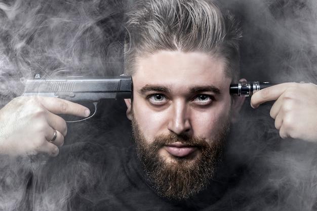 Het gezicht van een man met een pistool bevestigd aan zijn slaap en aan de andere kant een elektronische sigaret, omgeven door rook, roken doodt het concept, close-up
