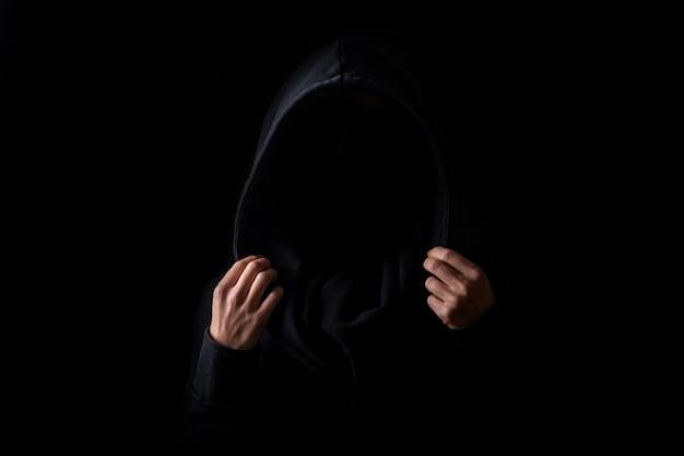 Het gezicht van een vrouw is niet zichtbaar in een zwart gewaad dat de kap met haar handpalmen op een zwarte achtergrond houdt.