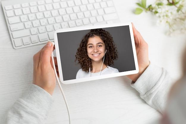 Het gezicht van het meisje op het tabletscherm. online conferentie. webinar.