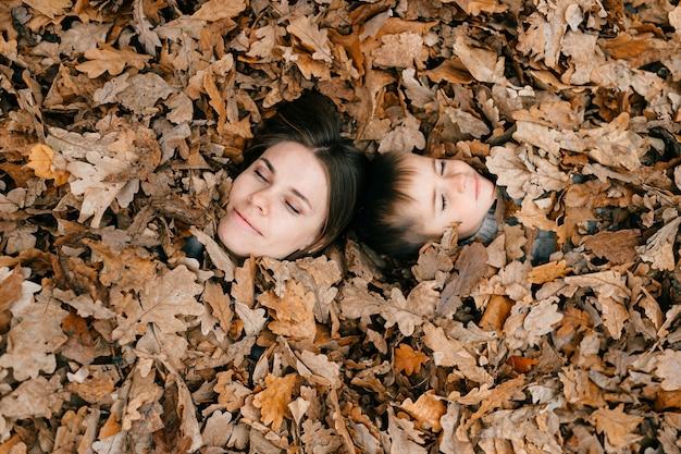 Het gezicht van moeder en zoon tussen bladeren