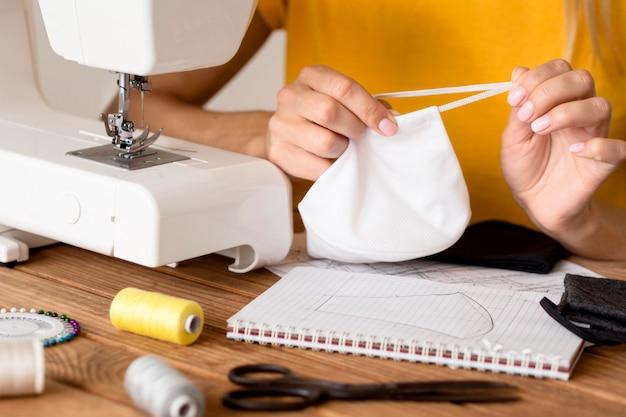 Het gezichtsmasker van de vrouwenholding zij naait op machine