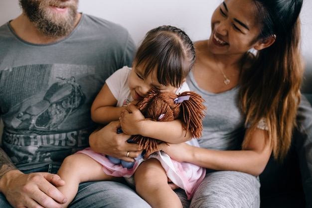 Het gezin brengt tijd thuis door. een kind knuffelt een pop