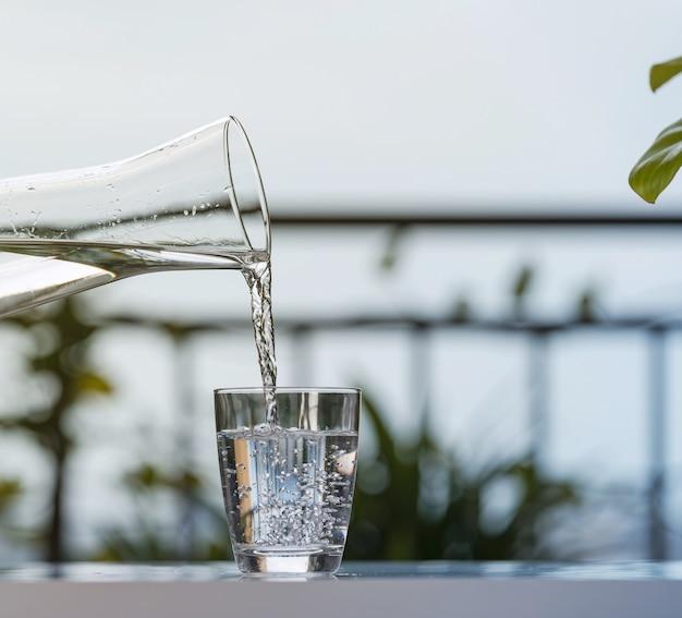 Het gieten drinkt water van fles in glas bij tuinhuis