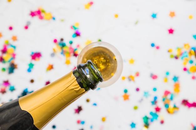 Het gieten van champagne in glas op lichte lijst