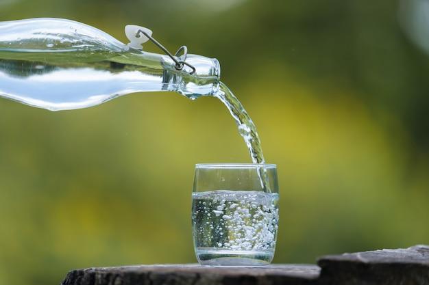 Het gieten van de hand drinkt water van fles in glas met natuurlijke achtergrond