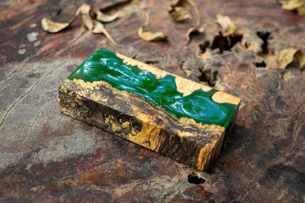 Het gieten van groene epoxyhars burl houten kubus op de oude achtergrond van de lijstkunst