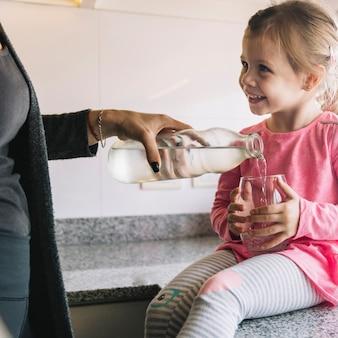 Het gietende water van de vrouwenhand in glas voor haar gelukkige dochter