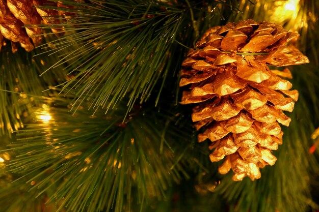 Het glanzende goudkleurige droge denneappelornament hangen op fonkelende kerstboom