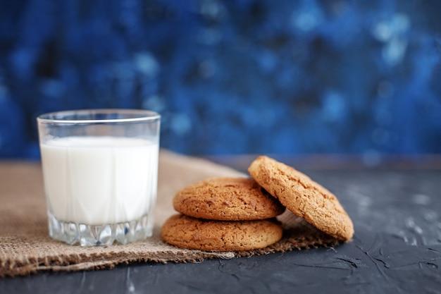 Het glas melk en smakelijke havermoutkoekjes.
