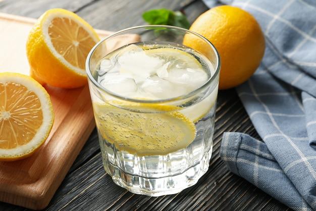 Het glas met limonade en ingrediënten op houten oppervlakte, sluit omhoog