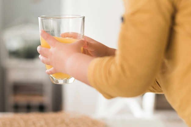 Het glas van de jongensholding jus d'orange