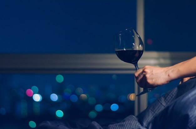 Het glas van de persoonsholding rode wijn op bed
