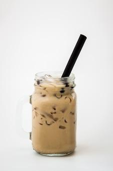 Het glas van de theemelkthee en boba borrelen koude drank op witte achtergrond, isoleren bevroren melkthee