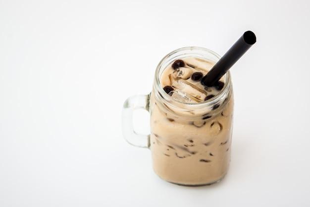 Het glas van de theemelkthee en boba borrelt koude drank op witte achtergrond, isoleert bevroren melkthee en boba bel