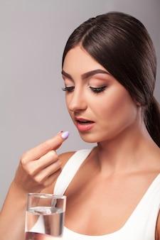 Het glas van de vrouwenholding water en het nemen van capsule