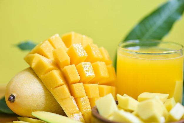 Het glas van het mangosap met mangoplak op mangobladeren van het fruitconcept van de boom tropisch zomer - zoete rijpe mango's