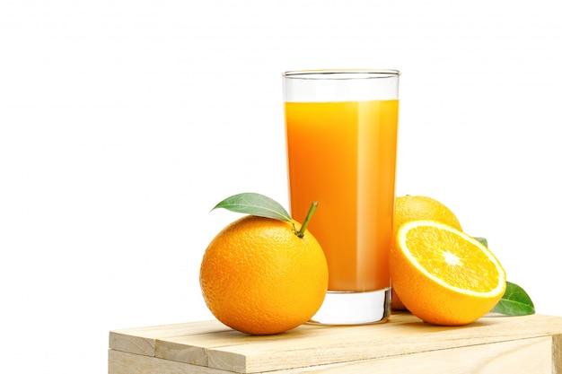 Het glas vers jus d'orange met groep sinaasappel op een houten doos isoleert op witte muur, selectieve nadruk op glas.