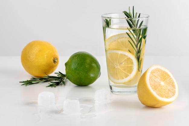 Het glas water met schijfjes citroen, rozemarijn en ijs.