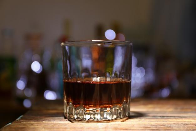 Het glas whisky op houten lijst, sluit omhoog. wazig lights achtergrond