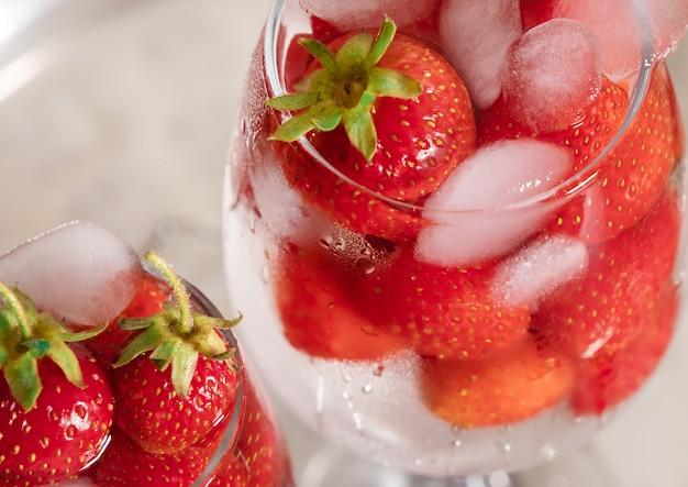 Het glas witte van de achtergrond aardbeidrank tropische bladeren cocktailijs