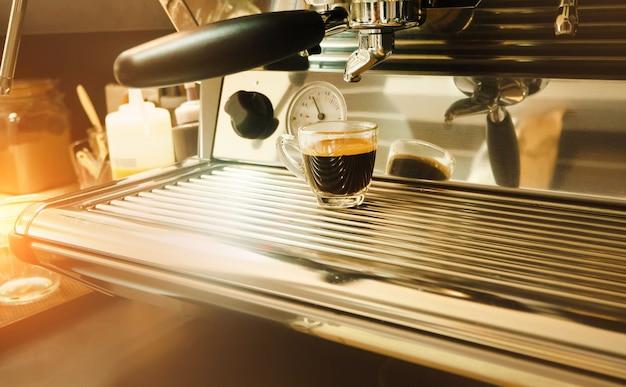 Het glas zwarte koffiekop gezet op koffiemachine