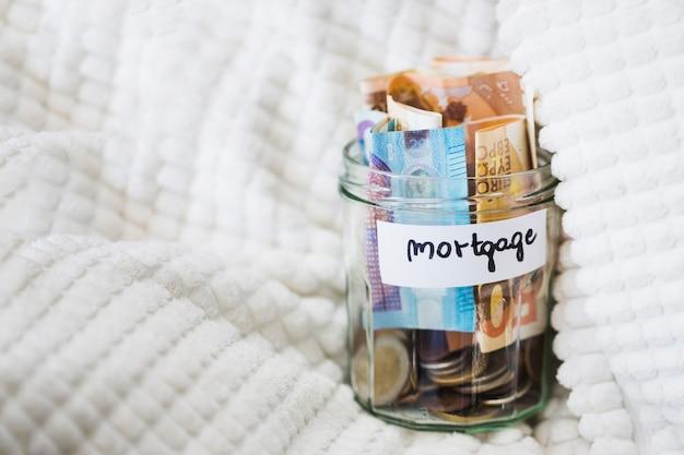 Het glaskruik van de hypotheek met euro nota's en muntstukken op witte deken