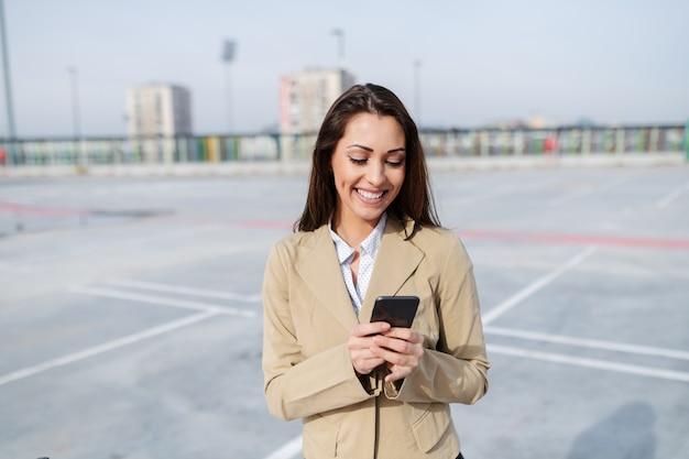 Het glimlachen aantrekkelijk glimlachend kaukasisch brunette gekleed in beige jasje die zich op parkeerterrein bevinden en slimme telefoon met behulp van.