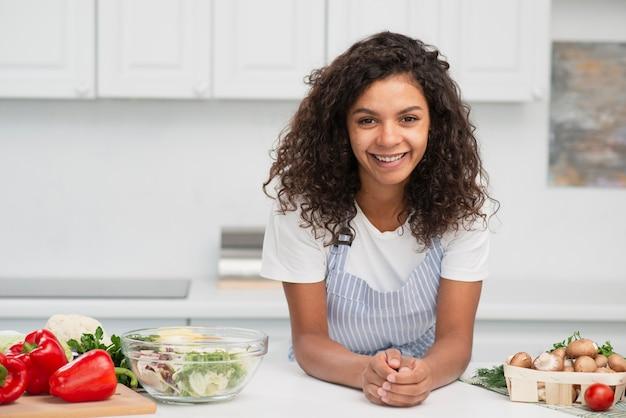 Het glimlachen afro het amerikaanse vrouw stellen naast groenten