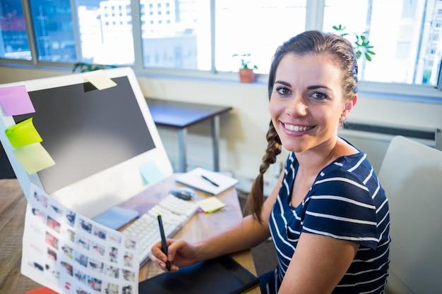 Het glimlachen brunette die met foto's en becijferaar werken
