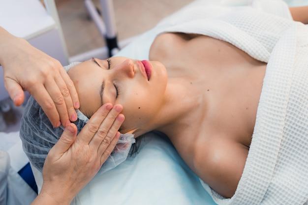 Het glimlachen brunette die van een hoofdmassage in health spa genieten