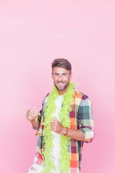 Het glimlachen de champagnefluit van de mensenholding het stellen tegen roze achtergrond