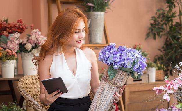 Het glimlachen de mooie orde van de bedrijfsvrouwencontrole in bloemenwinkel