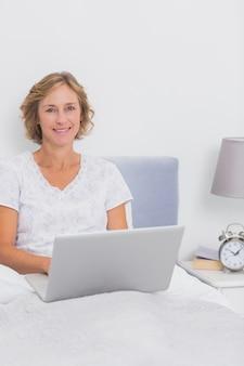 Het glimlachen de zitting van de blondevrouw in bed die laptop met behulp van