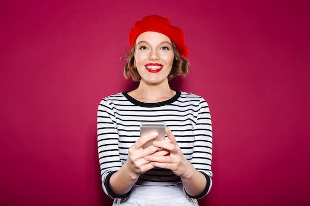 Het glimlachen gsm smartphone van de vrouwenholding en het bekijken de camera over roze