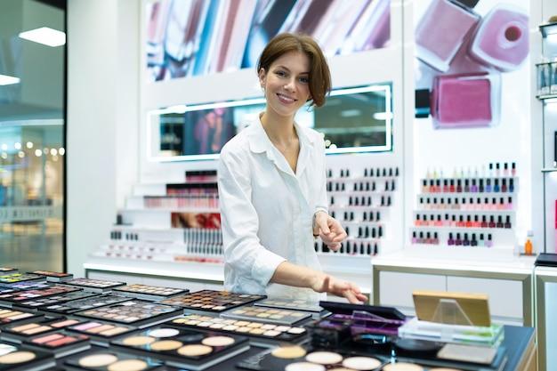 Het glimlachen het europese vrouw testen maakt omhoog bij reusachtige schoonheidsmiddelenopslag