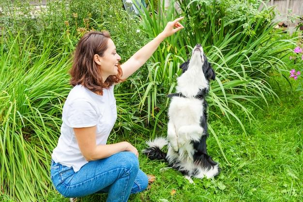 Het glimlachen het jonge aantrekkelijke vrouw spelen met leuke puppyhond border collie in de zomertuin of stadspark. meisje training truc met hond vriend. dierenverzorging en dieren concept.